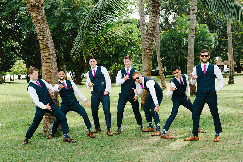 Our Groom, Daniel and His Guys, Clad in Navy Blue Suits Accented With Purple Ties and Tropical Print Socks Ham It Up Under Palm Trees.  Paying Homage to Kauai!