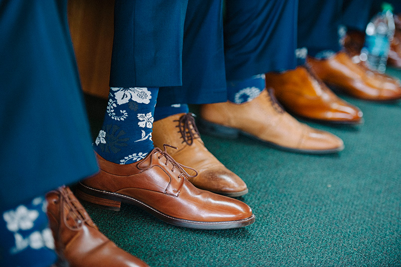 Paying Homage to the Islands.   Groomsmen Rocking Blue Hawaiian Print Socks and Tan Shoes.