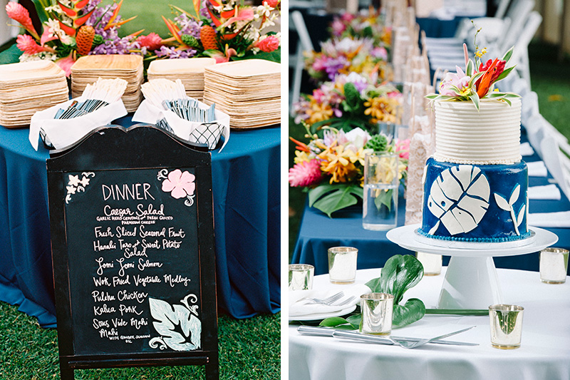Hawaiian Dinner Menu Board Flanked By Navy Blue Tables and A Tropical Leaf-Inspired Blue and White Cake.