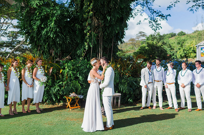 Bride and Groom Embrace Under A Towering Ear Pod Tree, Surrounded by Groomsmen and Bridesmaids