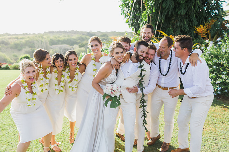 "We're Married!   Spirited Group Wearing White and Green Orchid Lei and Kukui Nut Lei, Hugs Bride and Groom After Saying ""I Do"""