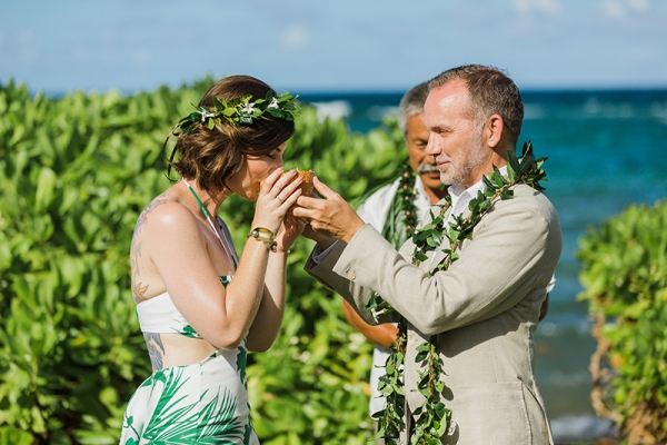 Groom Shares Coconut Water with Bride During Their Hawaiian Inspired Wedding Ceremony in Kauai, Hawaii