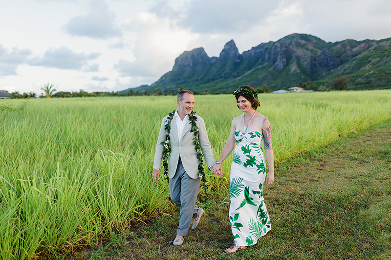 Bride and Groom Enjoying a Walk Through Green Fields with Mountains in the Distance
