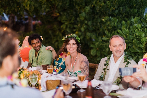 Bride and Groom Enjoying Dinner, Surrounded by Tropical Fauna and Close Friends and Family in Kauai