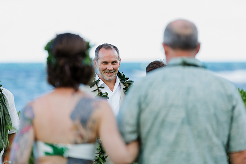 A glimpse of Groom's happy face as Bride and Dad reaches altar with Anahola Beach in background