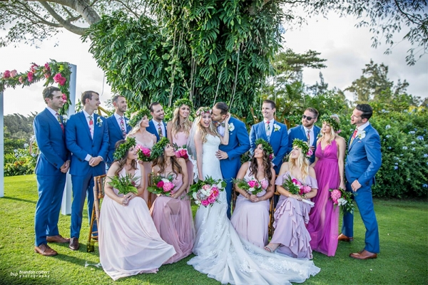 Groomsmen in Navy Blue and Bridesmaids in Shades of Pink Posing with Bride and Groom After Saying I Do