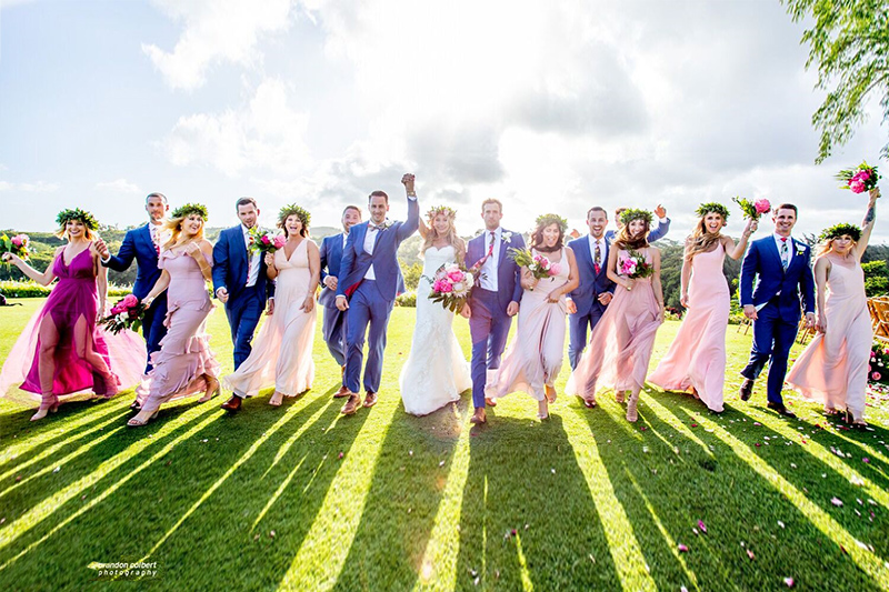 A Jubilant Bridal Party of Guys Wearing Navy Blue Suits and Girls in Shades of Pink