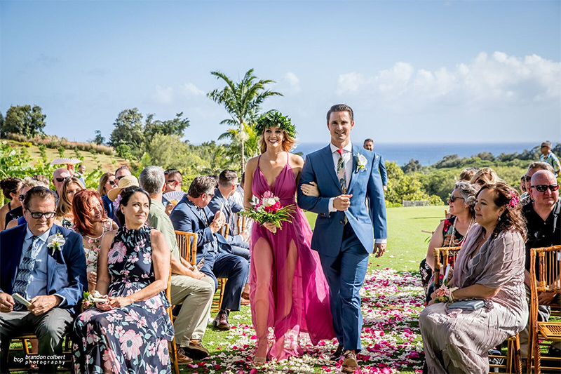Tropical Flower Bedecked Bridesmaid Walk Hand In Hand With Handsome Groomsman in a Tropical Setting