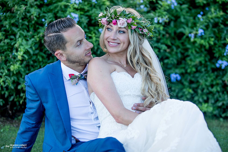 Handsome Groom Embraces His Lovely Bride Wearing A Tropical Flower Headband